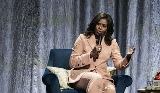 """Former U.S. first lady Michelle Obama talks on stage, at the Royal Arena in connection with her book tour for her biography """"Becoming"""" in Copenhagen, Denmark, Tuesday, April 9, 2019. (Martin Sylvest/Ritzau Scanpix via AP)"""
