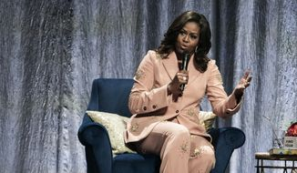"""Former US first lady Michelle Obama talks on stage, at the Royal Arena in connection with her book tour for her biography """"Becoming"""" in Copenhagen, Denmark, Tuesday, April 9, 2019. (Martin Sylvest/Ritzau Scanpix via AP)"""