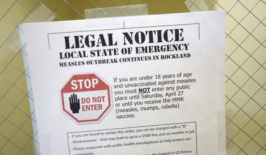 FILE - This Wednesday, March 27, 2019 file photo shows a sign explaining the local state of emergency because of a measles outbreak at the Rockland County Health Department in Pomona, N.Y. Measles is spread through the air when an infected person coughs or sneezes. It's so contagious that 90 percent of people who aren't immunized are infected if exposed to the virus, according to the Centers for Disease Control and Prevention. (AP Photo/Seth Wenig)