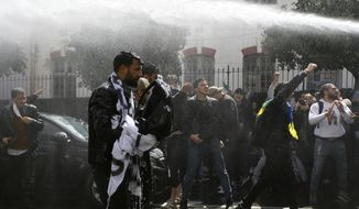 Algerian police forces use a water cannon as students demonstrate in Algiers, Tuesday, April 9, 2019. Algerian police have fired tear gas and water cannon to break up a group of students protesting in the country's capital, less than an hour after the country's parliament chose an interim leader. (AP Photo/Anis Belghoul)