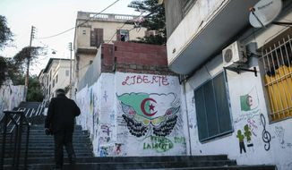 "A man walks past street art that reads ""liberty,"" supporting the current protest that has forced out longtime President Abdelaziz Bouteflika, in downtown Algiers, Algeria, Monday, April 8, 2019. The pro-democracy movement has forced out Bouteflika and demanded that other top figures leave too. (AP Photo/Mosa'ab Elshamy)"