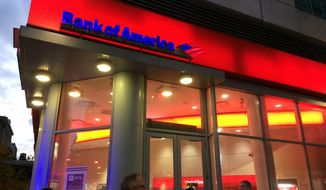 FILE- In this Nov. 6, 2017, file photo, people walk by a branch office of Bank of America in New York. Bank of America is raising its starting pay to $20 an hour over a two-year period, starting with a hike next month. The company said Tuesday, April 9, 2019, that it is raising its minimum hourly wage to $17 on May 1 and will continue to increase the pay until it hits $20 an hour in 2021. (AP Photo/Mark Lennihan, File)