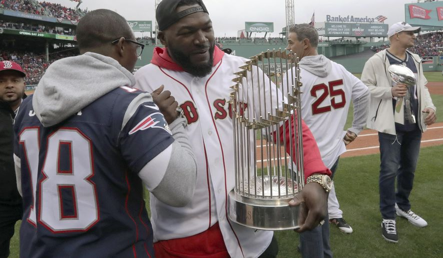 New England Patriots' Matthew Slater, left, clasps hands with former Boston Red Sox star David Ortiz as he holds the World Series trophy before the home opener baseball game between the Red Sox and the Toronto Blue Jays, Tuesday, April 9, 2019, in Boston. At right are former Red Sox star Mike Lowell (25) and retired New England Patriots' Rob Gronkowski, far right. (AP Photo/Charles Krupa)