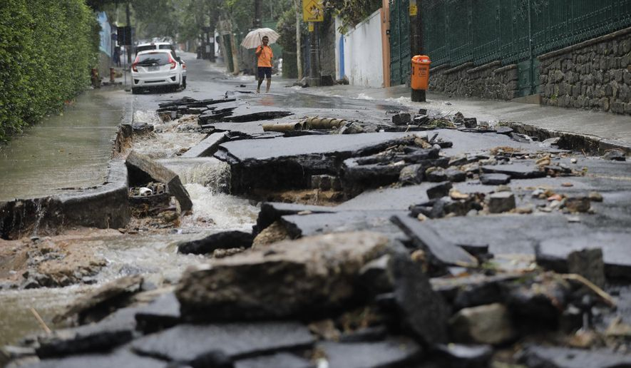 A man walks on a street damaged by heavy rains in the Jardim Botanico neighborhood in Rio de Janeiro, Brazil, Tuesday, April 9, 2019. Heavy rains blamed for the deaths of at least three people continued to fall on Rio on Tuesday as officials closed schools and urged people to avoid non-essential traffic. (AP Photo/Silvia Izquierdo)