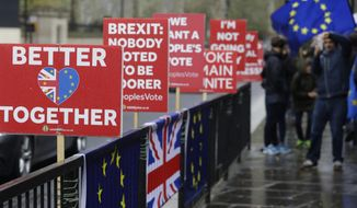 A passerby takes a picture of banners near parliament, in London, Tuesday, April 9, 2019. Prime Minister Theresa May has brought her case for a further delay to Britain's departure from the European Union to Berlin, while German and French officials are insisting that any extension to the deadline must come with strings attached and assurances from London. (AP Photo/Kirsty Wigglesworth)