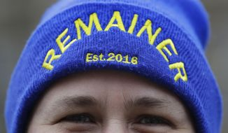An anti-Brexit campaigner wears a 'Remainer' hat near parliament, in London, Tuesday, April 9, 2019. Prime Minister Theresa May has brought her case for a further delay to Britain's departure from the European Union to Berlin, while German and French officials are insisting that any extension to the deadline must come with strings attached and assurances from London. (AP Photo/Kirsty Wigglesworth)