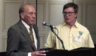 In this Monday, April 8, 2019, photo Frederick Osterhagen, left, speaks in support of the Burning Man festival while U.S. Bureau of Land Management field manager Mark Hall looks on during a public hearing in Sparks, Nev. Nearly 200 Burning Man backers packed a casino meeting room to mostly complain about new conditions and restrictions the government wants to place on the counter-culture festival in the northern Nevada desert. (AP Photo/Scott Sonner)