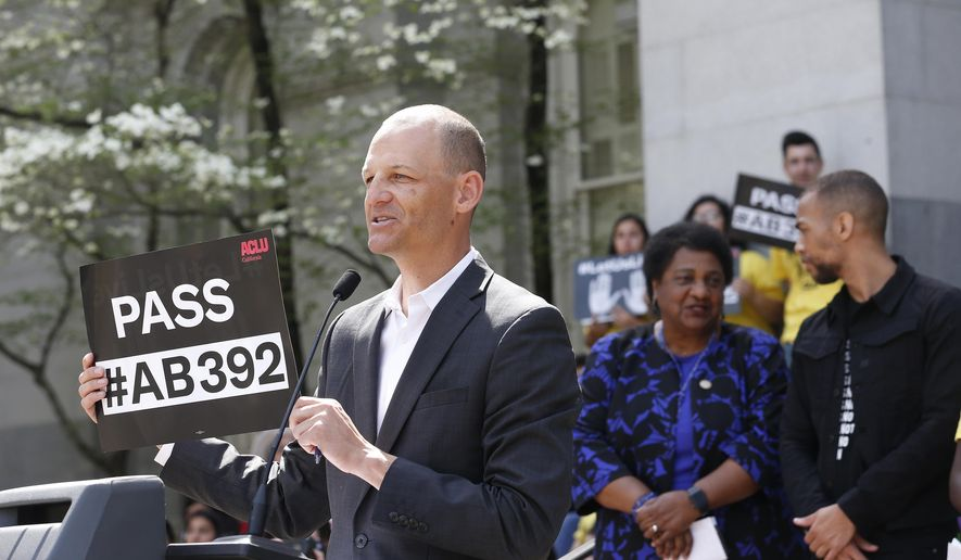 Assemblyman Kevin McCarty, D-Sacramento, displays a sign for a proposed measure to limit the use of deadly force by police during a rally at the Capitol, Monday, April 8, 2019, in Sacramento, Calif. The bill, AB392, co-authored by McCarty and Assemblywoman Shirley Weber, D-San Diego,, second from right, would require officers to use de-escalation tactics and allow the use of deadly force when it is necessary to prevent immediate harm to themselves or others. The measure faces heavy opposition from law enforcement organizations, which blocked a similar Senate-approved bill last year. (AP Photo/Rich Pedroncelli)