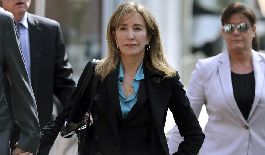 FILE - This April 3, 2019 file photo shows actress Felicity Huffman arriving at federal court in Boston to face charges in a nationwide college admissions bribery scandal. Huffman is facing a prison sentence after agreeing Monday to plead guilty to one count of conspiracy and fraud for paying a consultant $15,000 disguised as a charitable donation to boost her daughter's SAT score. Prosecutors are seeking four to 10 months of confinement, and experts different on whether the plea, and Huffman's subsequent apology taking full responsibility for her actions, will lead to a career rebound or retreat. (AP Photo/Charles Krupa, File)