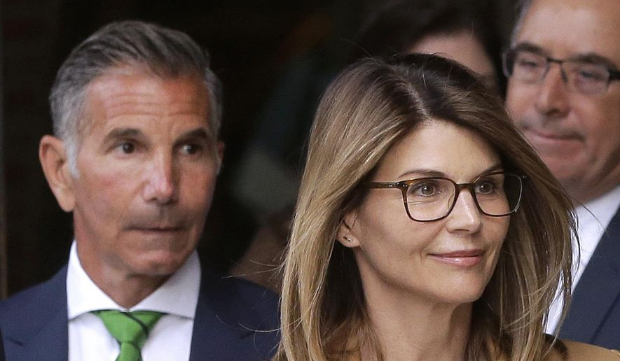 Actress Lori Loughlin, front, and husband, clothing designer Mossimo Giannulli, left, depart federal court in Boston after facing charges in a nationwide college admissions bribery scandal, April 3, 2019. On Tuesday, April 9, Loughlin and Giannulli were among 16 prominent parents indicted on an additional charge of money laundering conspiracy in the case. (AP Photo/Steven Senne) ** FILE **