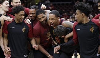 Teammates tackle Cleveland Cavaliers' Channing Frye after an NBA basketball game against the Charlotte Hornets, Tuesday, April 9, 2019, in Cleveland. Frye is retiring after 13 seasons. Charlotte won 124-97. (AP Photo/Tony Dejak)