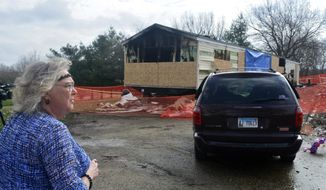 In this Sunday, April 7, 2019 photo, Marie Chockley, a resident of the Timberline Trailer Court, north of Goodfield, Ill., surveys the damage that was caused by a Saturday night fire that killed five residents in a mobile home. (Kevin Barlow/The Pantagraph via AP)
