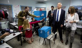 Blue and White party leader Benny Gantz, right, casts his vote with his wife Revital Gantz left, and former Israeli Chief of Staff Benny Gantz during Israel's parliamentary elections in Rosh Haayin, Israel, Tuesday, April 9, 2019. (AP Photo/Sebastian Scheiner)