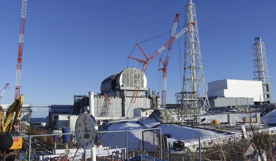 FILE - In this Jan. 25, 2018, file photo, an installation of a dome-shaped rooftop cover housing key equipment is near completion at Unit 3 reactor of the Fukushima Dai-ich nuclear power plant ahead of a fuel removal from its storage pool in Okuma, Fukushima Prefecture, northeast Japan.  Japan has partially lifted an evacuation order in one of the two hometowns of the tsunami-wrecked Fukushima nuclear plant for the first time since the 2011 disaster. The action taken Wednesday, April 10, 2019, allows people to return about 40 percent of Okuma. The other hometown, Futaba, remains off-limits as are several other towns nearby.(AP Photo/Mari Yamaguchi, File)