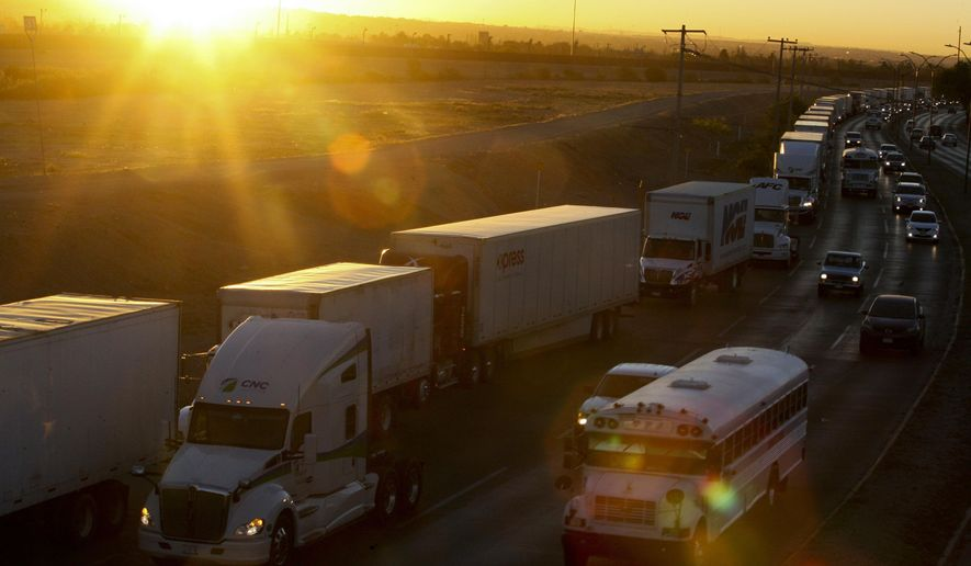 A row of trucks wait to cross the border with the United States in Ciudad Juarez, Mexico, Tuesday, April 9, 2019. The Trump administration has reassigned so many inspectors from U.S.-Mexico border crossings that it has caused huge traffic backups for truckers who are waiting in line for hours and in some case days to get shipments to the U.S. (AP Photo/Christian Torres)