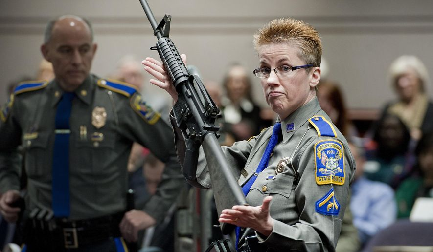 FILE - In this Jan. 28, 2013, file photo, firearms training unit Detective Barbara J. Mattson, of the Connecticut State Police, holds a Bushmaster AR-15 rifle, the same make and model used by Adam Lanza in the 2012 Sandy Hook School shooting, during a hearing at the Legislative Office Building in Hartford, Conn. A divided Connecticut Supreme Court ruled that gun maker Remington can be sued over how it marketed the Bushmaster rifle used in the massacre.  In court documents filed Friday, April 5, 2019, Remington notified the Connecticut Supreme Court of its plans to pursue an appeal with the Supreme Court of the United States. (AP Photo/Jessica Hill, File)