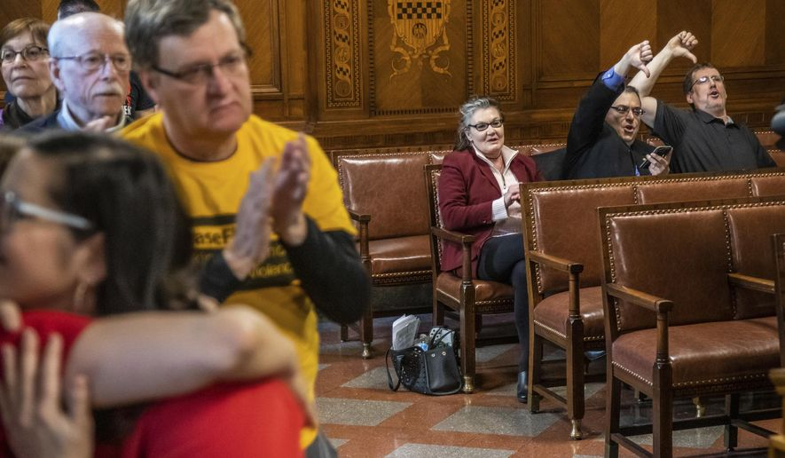 Opponents give a thumbs down, as others applaud, after the Pittsburgh City Council voted 6-3 to pass gun-control legislation, Tuesday, April 2, 2019, in Pittsburgh. The bill, introduced in the wake of the synagogue massacre last October, places restrictions on military-style assault weapons like the AR-15 rifle that authorities say was used in the attack that killed 11 and wounded seven.(Andrew Rush/Pittsburgh Post-Gazette via AP)