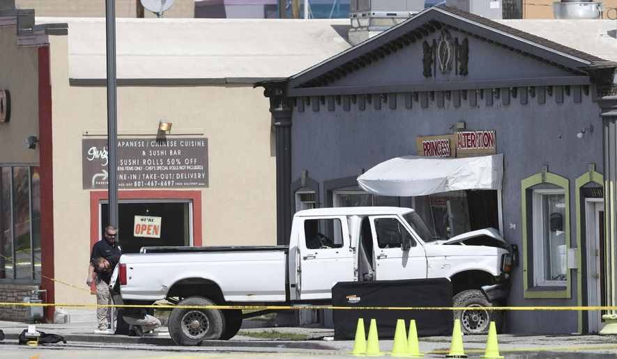 A white pickup truck that crashed into Princess Alterations, 3339 S. State in South Salt Lake is pictured on Monday April 8, 2019. The driver of the pickup, who was suspected of committing two robberies and who apparently opened fire outside the Sheraton Hotel in downtown Salt Lake City earlier Monday, died after leading police on a chase that ended in a crash and a hail of bullets. (Steve Griffin/The Deseret News via AP)
