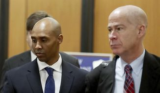 Former Minneapolis Police Officer Mohamed Noor, center, is accompanied by his attorneys Peter Wold, not pictured, and Thomas Plunkett, right, as he walks toward the Hennepin County Government Center for opening arguments of his trial Tuesday, April 9, 2019, in Minneapolis. (David Joles/Star Tribune via AP)