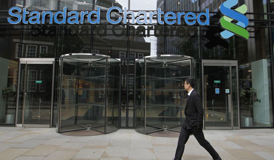 FILE - In this Aug 7, 2012, file photo a man walks by Standard Chartered bank in London. British financial services giant Standard Chartered Bank will pay $1.1 billion in fines to settle allegations by U.S. and British authorities that it attempted to evade U.S. sanctions imposed on Iran, Cuba, Burma and other nations. The settlement Tuesday,  April 9, 2019, was announced by the U.S. Treasury, the Federal Reserve and other bank regulators in the U.S. and Britain. (AP Photo/Sang Tan, File)