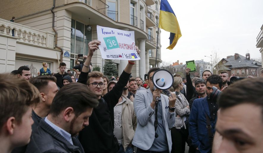 """Supporters of Ukrainian President Petro Poroshenko gather in front of Volodymyr Zelenskiy, Ukrainian actor and candidate's headquarters during a rally in Kiev, Ukraine, Tuesday, April 9, 2019. A poster reads """"Kryvyi Rih wants to know is Zelenskiy a drug addict?"""" (AP Photo/Efrem Lukatsky)"""