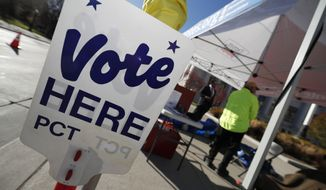FILE - In this Nov. 6, 2018, file photo a sign directs voters to the Denver Elections Division drop off location in front of the City/County Building in Denver. Colorado's Democrat-controlled Legislature is rushing a bill to have the state join others in casting its electoral votes for the winner of the national popular vote. (AP Photo/David Zalubowski, File)