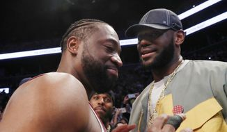 Miami Heat guard Dwyane Wade, left, chats with LeBron James before the Heat's NBA basketball game against the Brooklyn Nets, Wednesday, April 10, 2019, in New York. Wade retired after the game. (AP Photo/Kathy Willens)