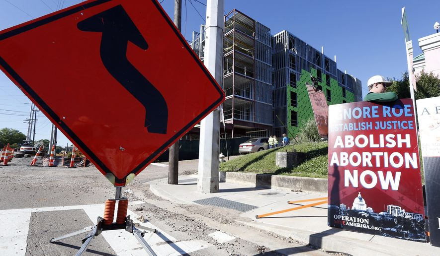 Abortion opponents stand outside the Jackson Women's Health Organization clinic, right, while construction on a hotel, background, continues in Jackson, Miss., Wednesday, April 10, 2019. The clinic is the only medical facility that performs abortions in the state. The state legislature recently passed a law that would ban most abortions after a fetal heartbeat is detected, meaning as early as six weeks. (AP Photo/Rogelio V. Solis)