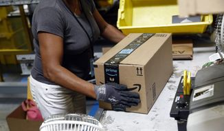 FILE - In this Aug. 3, 2017, file photo, an Amazon employee applies tape to a package before shipment at an Amazon fulfillment center in Baltimore. The online shopping giant, which already works with BP and Shell, has been trying to woo more oil and gas companies to use its technology to help them find drillable oil faster, angering workers who have been pushing Amazon to do more to combat climate change. (AP Photo/Patrick Semansky, File)