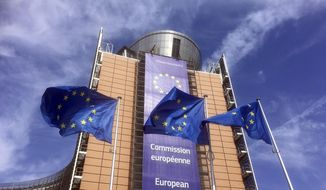 European Union flags flap in the wind outside EU headquarters in Brussels, Wednesday, April 10, 2019. European Union leaders meet Wednesday in Brussels for an emergency summit to discuss a new Brexit extension. (AP Photo/Virginia Mayo)
