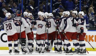 The Columbus Blue Jackets celebrates their 4-3 win over the Tampa Bay Lightning during Game 1 of an NHL Eastern Conference first-round hockey playoff series Wednesday, April 10, 2019, in Tampa, Fla. (AP Photo/Chris O'Meara)