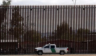 In this April 5, 2019, file photo, a U.S. Customs and Border Protection vehicle sits near the wall as President Donald Trump visits a new section of the border wall with Mexico in Calexico. (AP Photo/Jacquelyn Martin)