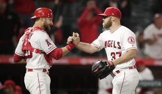 Los Angeles Angels relief pitcher Cody Allen, right, and catcher Jonathan Lucroy celebrate the team's 11-8 win over the Milwaukee Brewers in a baseball game, Tuesday, April 9, 2019, in Anaheim, Calif. (AP Photo/Jae C. Hong)