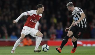 Arsenal's Mesut Ozil, left, competes for the ball with Newcastle's Paul Dummett during the English Premier League soccer match between Arsenal and Newcastle United at Emirates stadium in London, Monday, April 1, 2019. (AP Photo/Kirsty Wigglesworth)