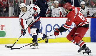 Washington Capitals' Alex Ovechkin (8), of Russia, takes a shot in goal as Carolina Hurricanes' Trevor van Riemsdyk (57) defends during the second period of an NHL hockey game in Raleigh, N.C., Thursday, March 28, 2019. (AP Photo/Gerry Broome)