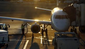 FILE - In this Dec. 8, 2018, file photo, a worker fuels a Delta Connection regional airlines passenger jet at Logan International Airport in Boston. Delta Air Lines Inc. reports financial results Wednesday, April 10, 2019.(AP Photo/Bill Sikes, File)