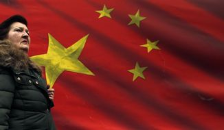 In this photo taken Friday, March 1, 2019, a woman walks by Chinese flag placed on a street in Belgrade, Serbia. Chinese investments have been booming throughout Central and Eastern Europe's cash-strapped developing countries, even as European Union officials scramble to counter Beijing's mounting economic and political influence the EU has branded a ''systematic rival.'' (AP Photo/Darko Vojinovic)