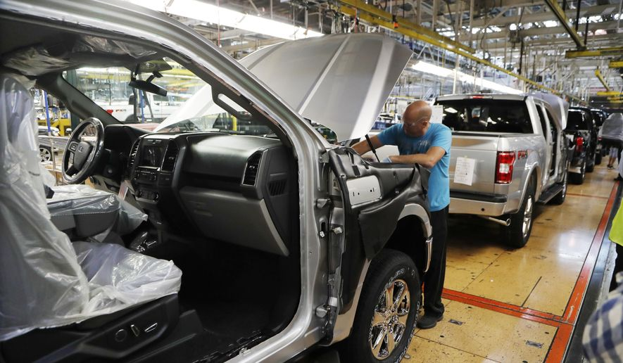 In this Sept. 27, 2018, file photo a United Auto Workers assemblyman works on a 2018 Ford F-150 truck being assembled at the Ford Rouge assembly plant in Dearborn, Mich. Ford is recalling 327,000 F-Series pickup trucks in North America for a second time to fix problems with engine block heater cables that can cause fires. The recall covers F-150s from 2015 through 2019, as well as Super Duty trucks from 2017 through 2019. (AP Photo/Carlos Osorio, File) **FILE**