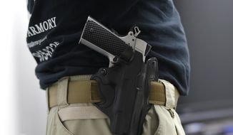 In this Jan. 5, 2016, file photo, Mike Weinstein, director of training and security at the National Armory gun store and gun range, wears a Ruger 1911 handgun in a holster as he teaches a concealed weapons permit class in Pompano Beach, Fla. Florida might grant authority to 2 million civilians who can lawfully carry guns tucked in waistbands, under jackets or inside purses into restaurants, shopping malls and elsewhere. (AP Photo/Lynne Sladky, File)