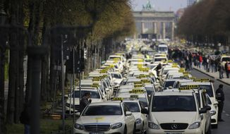 Berlin taxi drivers block the boulevard 'Strasse des 17. Juni', Street of June 17, in front of the Brandenburg Gate, during a protest in Berlin, Germany, Wednesday, April 10, 2019. Taxi driver protest against government plans over the growth of app-based ride-hailing services that they say threaten their livelihood. (AP Photo/Markus Schreiber)