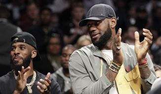 Chris Paul and LeBron James applaud during a ceremony at an NBA basketball game between the Brooklyn Nets and the Miami Heat, Wednesday, April 10, 2019, in New York. The pair were there to watch Heat guard Dwyane Wade play his last NBA game. (AP Photo/Kathy Willens)