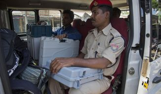 Indian polling officials and police with electronic voting machines and voter verifiable paper audit trail (VVPAT) sit inside a vehicle before heading to a polling station on the eve of the first phase of general election in Majuli, Assam, India, Wednesday, April 10, 2019. Voting will take place in seven phases over six weeks beginning Thursday. Nearly 900 million people, including 15.9 million first-time voters, are eligible to cast ballots in the world's largest democratic exercise. (AP Photo/Anupam Nath)