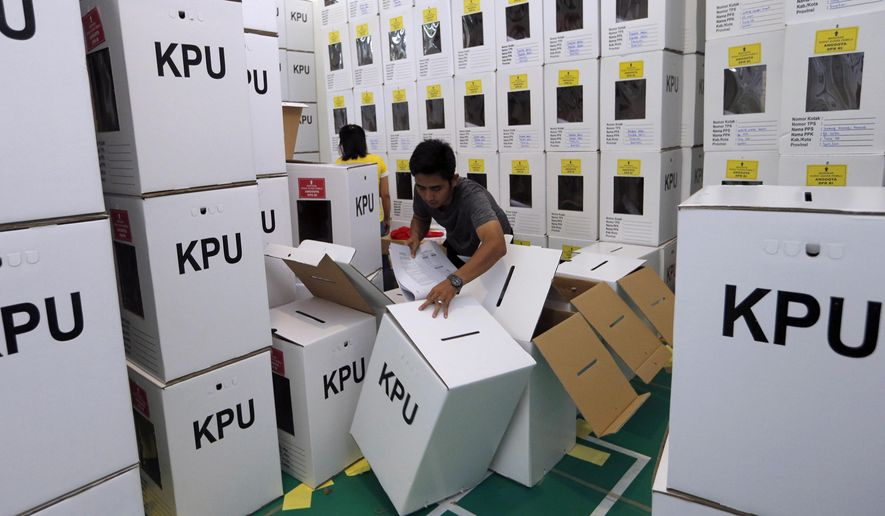 An Indonesian electoral worker prepares ballot in the boxes to be distributed to polling stations in Jakarta, Indonesia, Wednesday, April 10, 2019. The world's third-largest democracy is gearing up to hold its legislative and presidential elections on April 17. (AP Photo/Tatan Syuflana)