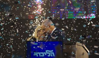 Israel's Prime Minister Benjamin Netanyahu and Likud party leader kisses his wife Sara in from of his supporters after polls for Israel's general elections closed in Tel Aviv, Israel, Wednesday, April 10, 2019. (AP Photo/Ariel Schalit)