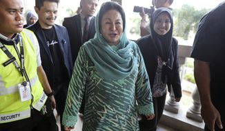 Rosmah Mansor, center, wife of former Malaysian Prime Minister Najib Razak, walks into courtroom at Kuala Lumpur High Court in Kuala Lumpur, Malaysia, Wednesday, April 10, 2019. Rosmah Mansor is expected to be charged in court pertaining to allegations of misappropriation linked to a solar energy project for rural schools.  (AP Photo/Vincent Thian)