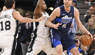 Dallas Mavericks' Dirk Nowitzki (41) drives against San Antonio Spurs' Rudy Gay, center, and Marco Belinelli during the second half of an NBA basketball game Wednesday, April 10, 2019, in San Antonio. San Antonio won 105-94. (AP Photo/Darren Abate)