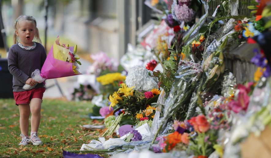 In this March 17, 2019, file photo, a girl carries flowers to a memorial wall following the mosque shootings in Christchurch, New Zealand. New Zealand's parliament on Wednesday passed sweeping gun laws which outlaw military-style weapons, less than a month after the nation's worst mass shooting left 50 dead and 39 wounded in two mosques in the South Island city of Christchurch. (AP Photo/Vincent Thian, File)