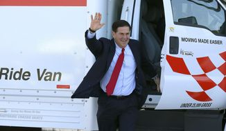 Republican Arizona Gov. Doug Ducey arrives at Arizona Capitol in a moving van prior to signing into law HB 2569 making Arizona the first state in the nation to provide universal recognition for occupational licenses Wednesday, April 10, 2019, in Phoenix. (AP Photo/Ross D. Franklin) **FILE**