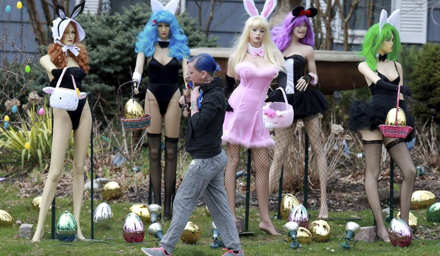 A woman walks carrying her dog past an Easter display in Clifton, N.J., Tuesday, April, 9, 2019.  A New Jersey woman unhappy with her neighbor's racy Easter display used some garden shears to damage it.But the display's owner says it will soon be back up. The display at a dental office in Clifton featured five mannequins dressed in lingerie, all holding Easter baskets and surrounded by Easter eggs. It had drawn mixed reviews from neighbors, as well as passers-by who stopped to take photos. ( Ed Murray/NJ Advance Media via AP)