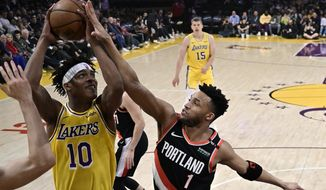 Los Angeles Lakers forward Jemerrio Jones, left, shoots as Portland Trail Blazers guard Evan Turner defends during the first half of an NBA basketball game Tuesday, April 9, 2019, in Los Angeles. (AP Photo/Mark J. Terrill)